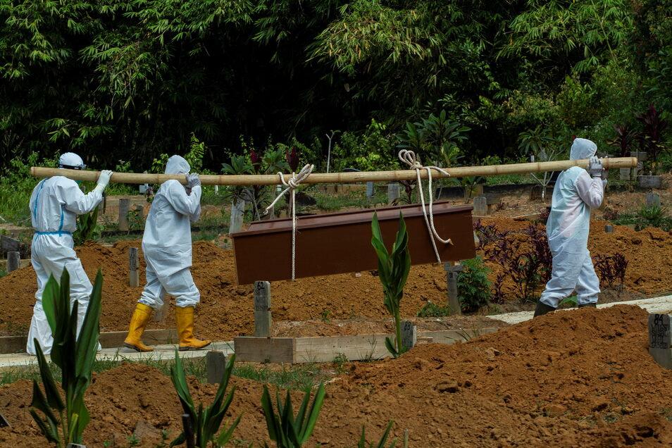 Indonesische Friedhofsarbeiter in Schutzausrüstung tragen einen Sarg mit dem Leichnam eines Corona-Toten während der Beerdigung auf einem Friedhof.