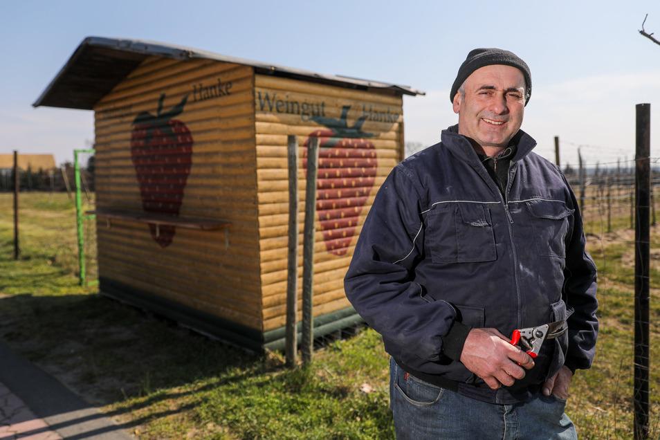 """Wein- und Obstbauer Frank Hanke steht vor einer geschlossenen Verkaufsbude. Franke baut unter anderem Erdbeeren der Sorte """"Korona"""" an."""