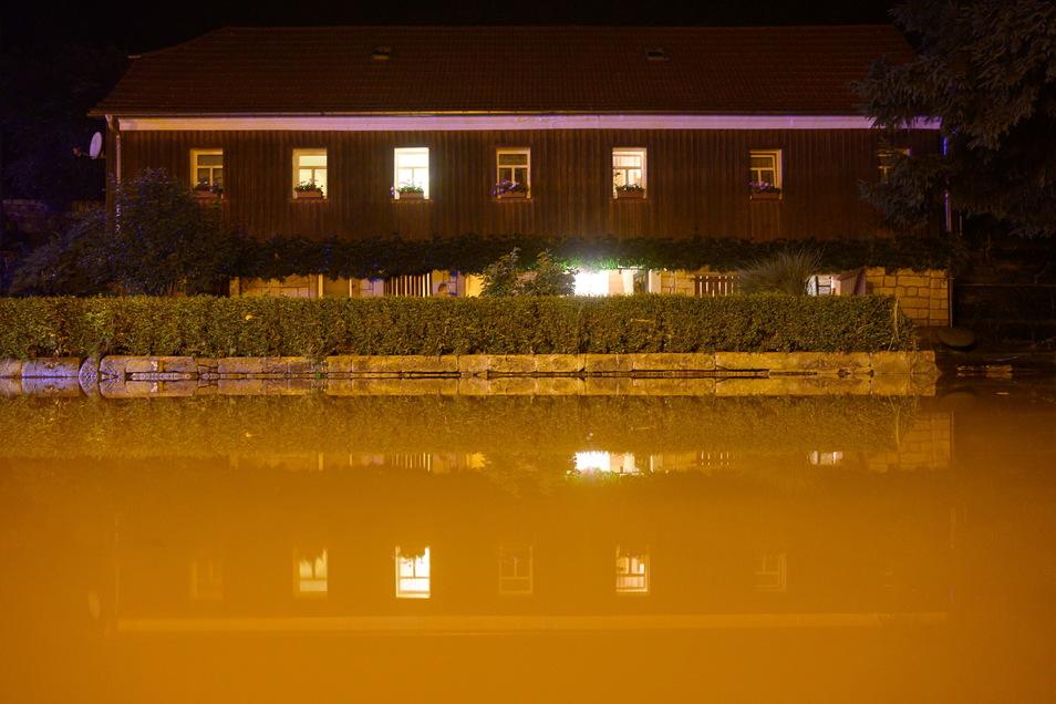 Eine Straße ist vor einem Wohnhaus in Bad Schandau mit Wasser der Kirnitzsch überflutet.