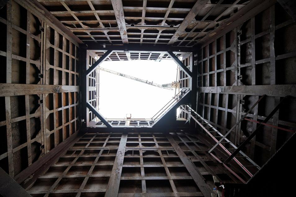 Ein Blick aus der Baugrube in luftige Höhen, wo der Kran bald das nächste Rohrstück einhebt.
