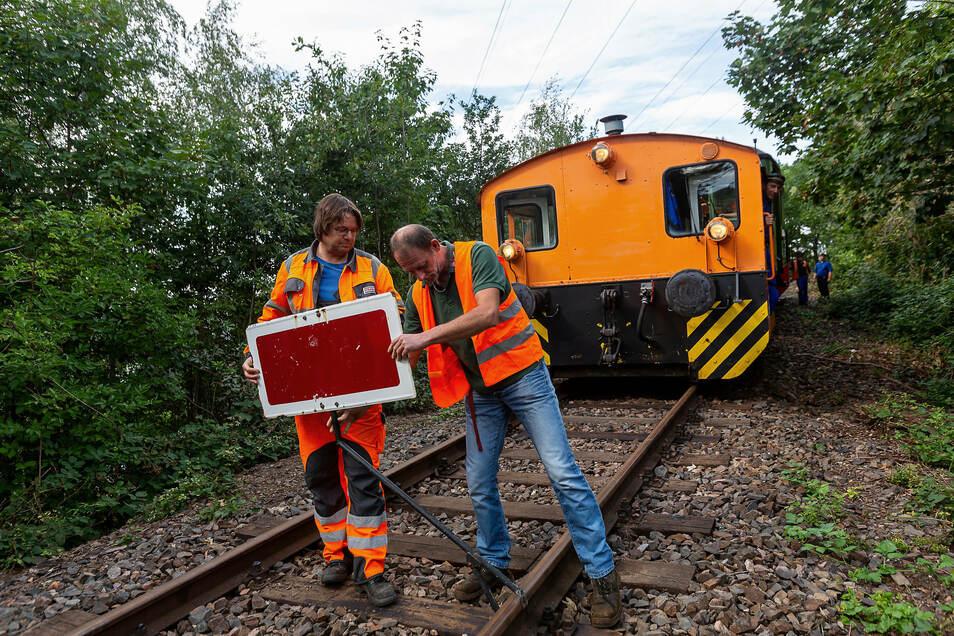 Strecke frei: Tilo Dinter, Ausbilder bei Strabag und Maik Schulze vom Windbergbahn-Verein entfernen das Sperrschild.
