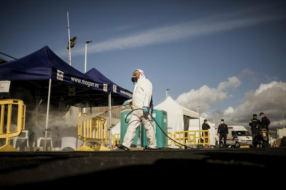 Ein Arbeiter desinfiziert am Montag im Hafen von Arguineguin das von Migranten genutzte Gebiet. Spanien hat den größten Teil des provisorischen Lagers für die vorübergehende Aufnahme von Migranten abgebaut. Mehr als drei Monate lang lebten Tausende von Mi