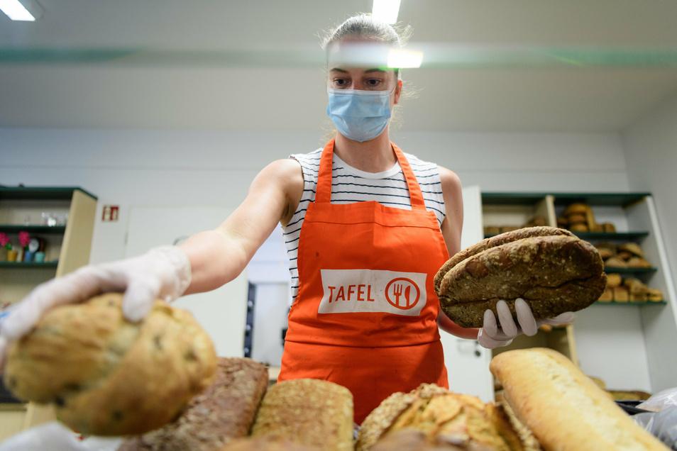 Eine ehrenamtliche Helferin bei der Potsdamer Tafel, stapelt vor Beginn der Ausgabe an Bedürftige Brot.