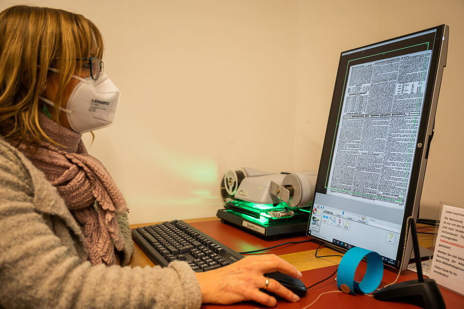 Karin Stichel liest eine Zeitung auf Mikrofilm ein. Die Zeitungsseiten sind als kleine Bilder auf dem Film festgehalten und können stark vergrößert und beleuchtet gut gelesen werden.