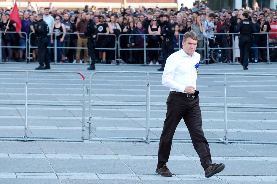 Vor hunderten Gegendemonstranten (im Hintergrund) gehtPoggenburg zu seinem Rednerpult.