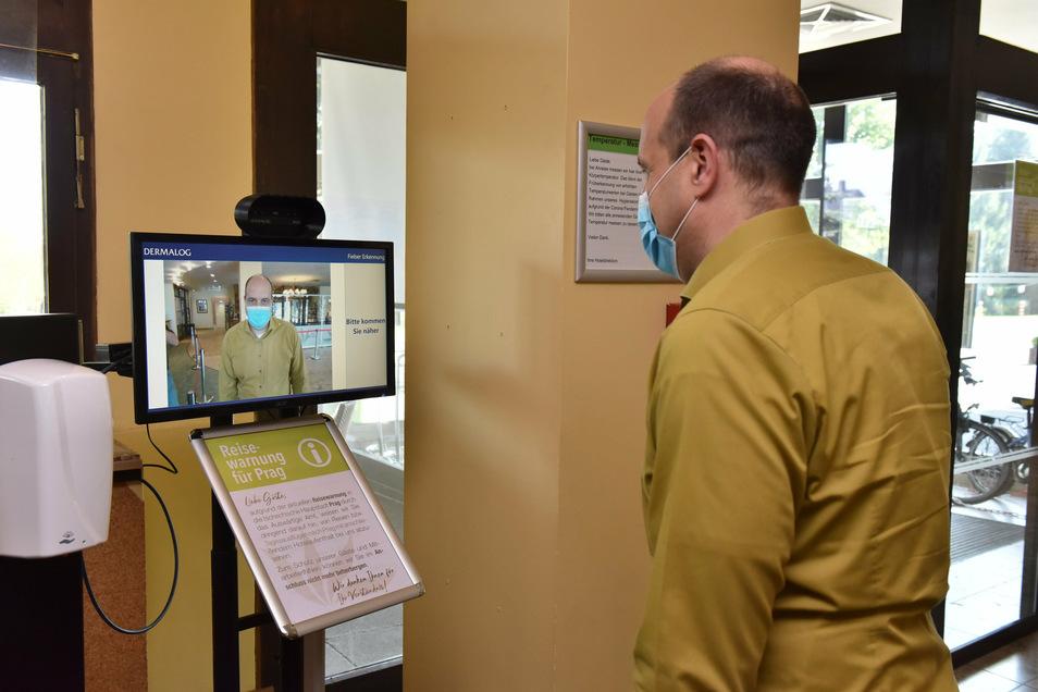 Uwe Metzler, der Hoteldirektor vom Ahorn Waldhotel Altenberg in Schellerhau, vor der Anlage zur Körper-Temperaturmessung an der Rezeption.