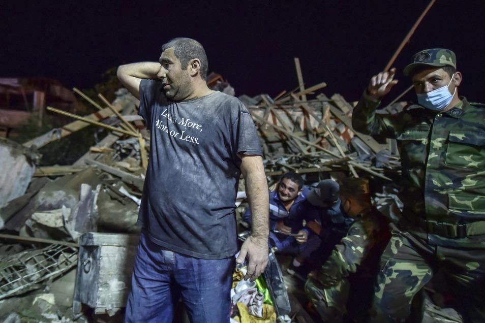 Aserbaidschan, Ganja: Aserbaidschanische Soldaten und Feuerwehrleute versuchen, Überlebende aus zerstörten Häusern in einem Wohngebiet zu retten.