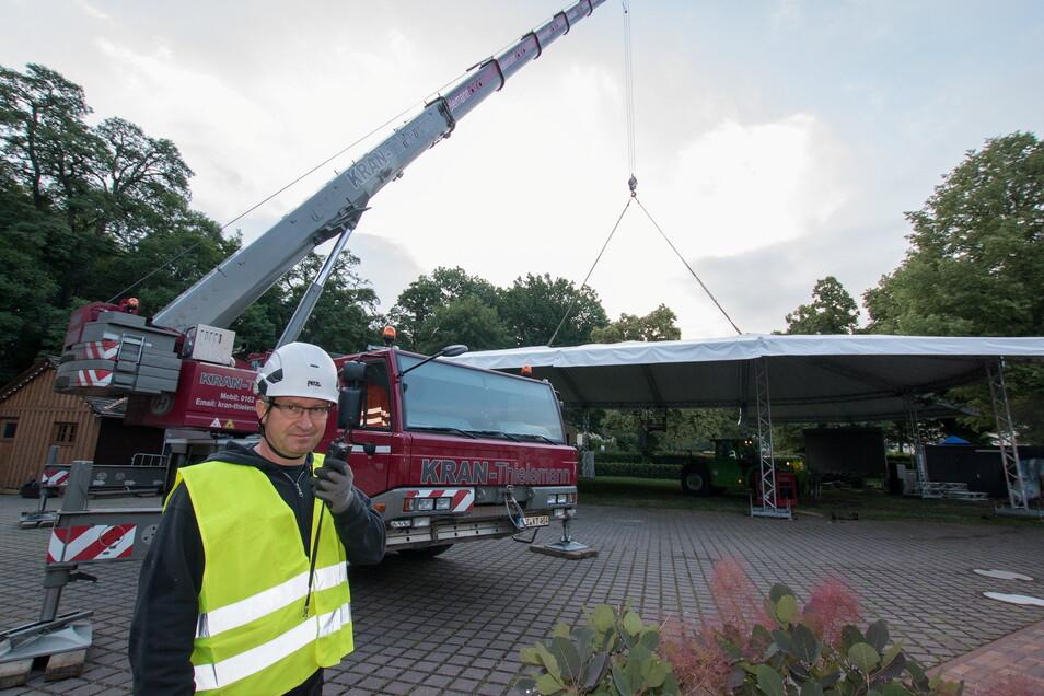 Mit einem Spezialkran wurde ein wetterfestes Zelt im Bürgergarten aufgestellt. Entwickler des Zeltes und Firmenchef Hartmut Welzel, gibt dem Kranführer über Funk Anweisungen.