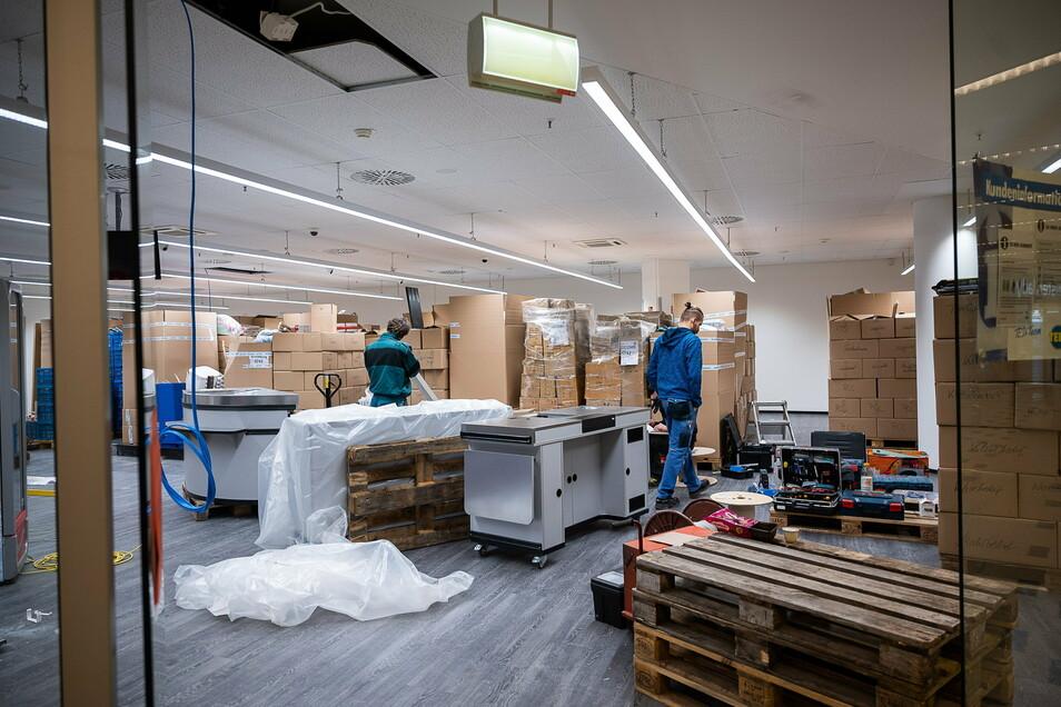 Die Ware ist verpackt in Kartons. Monteure bauen die neuen Regalsysteme auf.