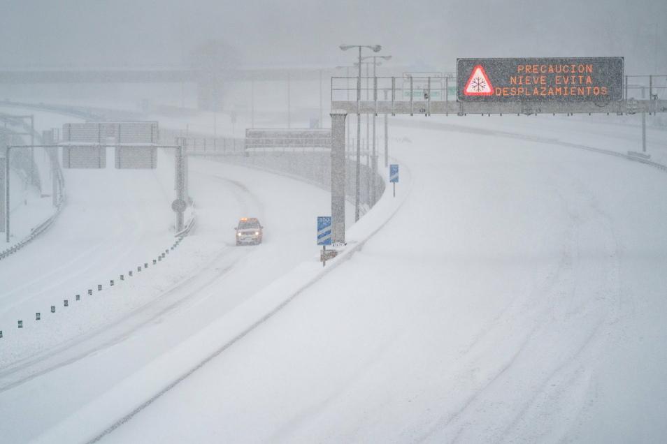 Ein Rettungsfahrzeug fährt auf der leeren, schneebedeckten Schnellstraße M-30.