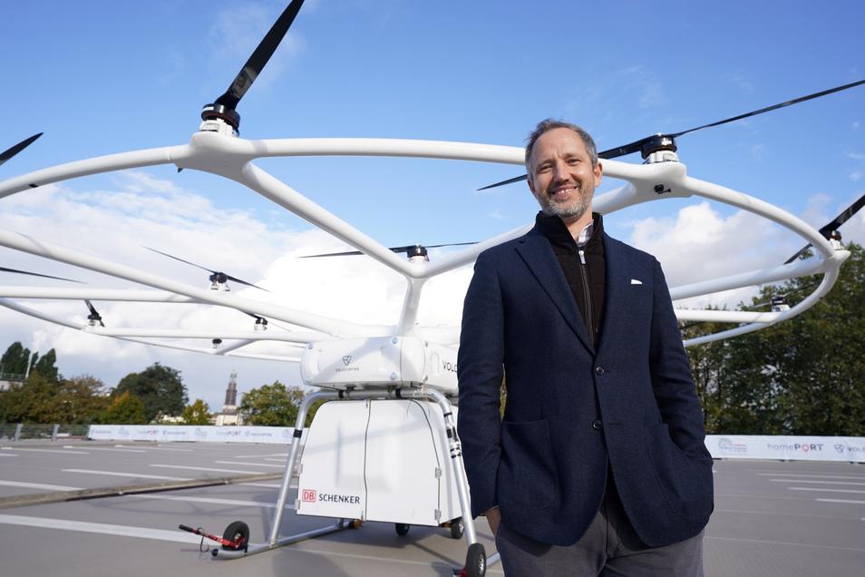 Florian Reuter, Geschäftsführer von Volocopter, steht nach dem Premierenflug im Hafen vor der Schwerlastdrohne Volodrone.