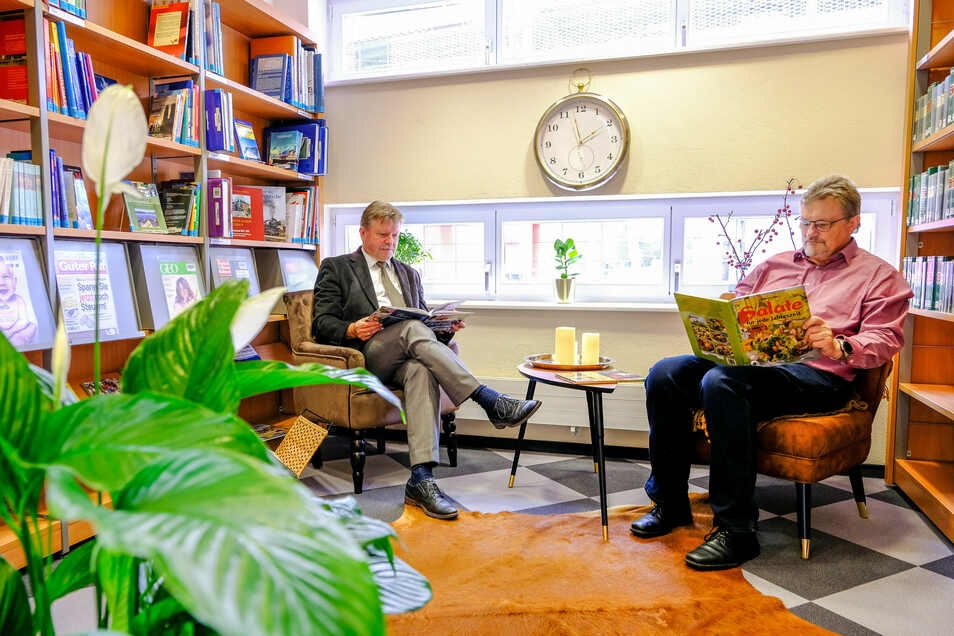 In der neuen Leseecke der Bibliothek (rechts) stöbern OB Bert Wendsche (l.) und ein Besucher in Büchern.