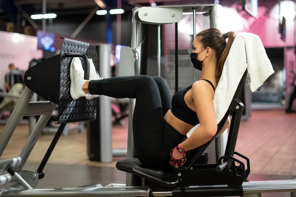Eine Frau trainiert mit Mundschutz in einem Fitnessstudio an einer Beinpresse.