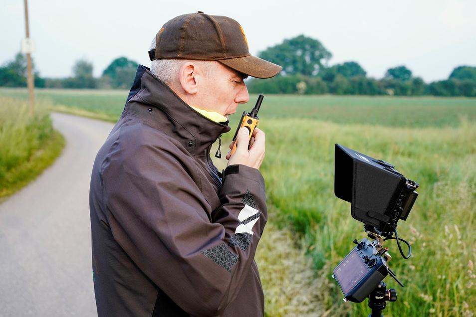 Michael Ehlers, Leiter der Rehkitz-Rettung Weinheim, steuert mit Hilfe eines Monitors eine Drohne über eine Wiese.