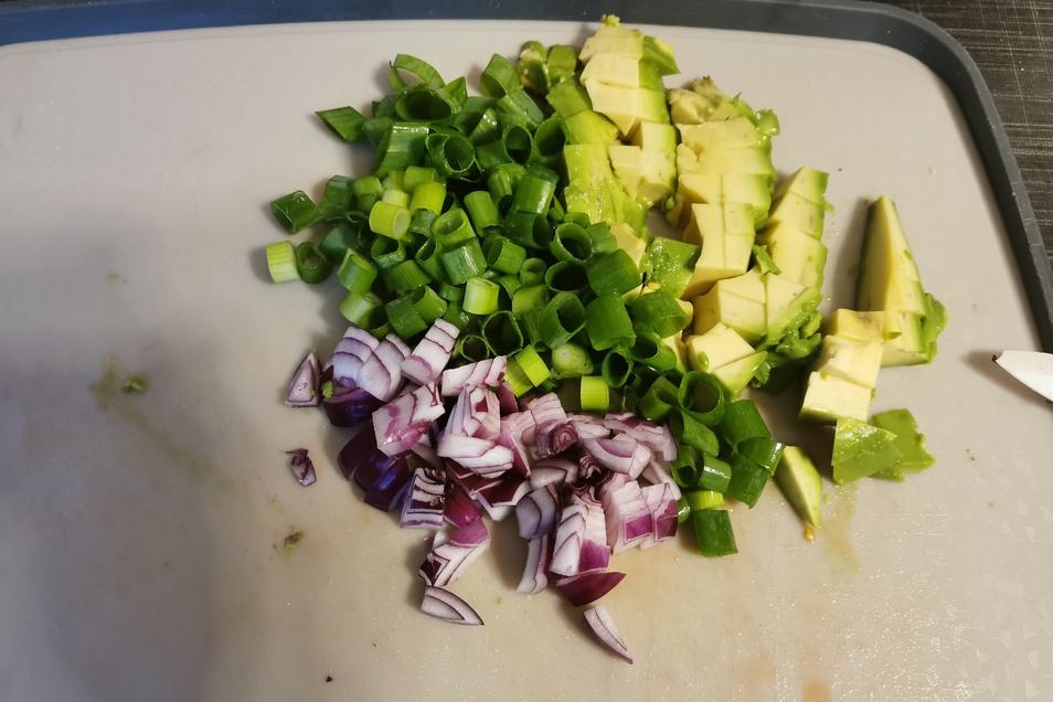 9. Schritt: Den Rest der roten Zwiebeln sowie eine halbe Avocado klein würfeln und Frühlingszwiebeln in Ringe schneiden.
