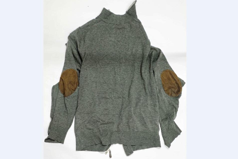 """Darunter trug er einen grauen Pullovermit Aufnähern der Marke """"New Sensation""""."""