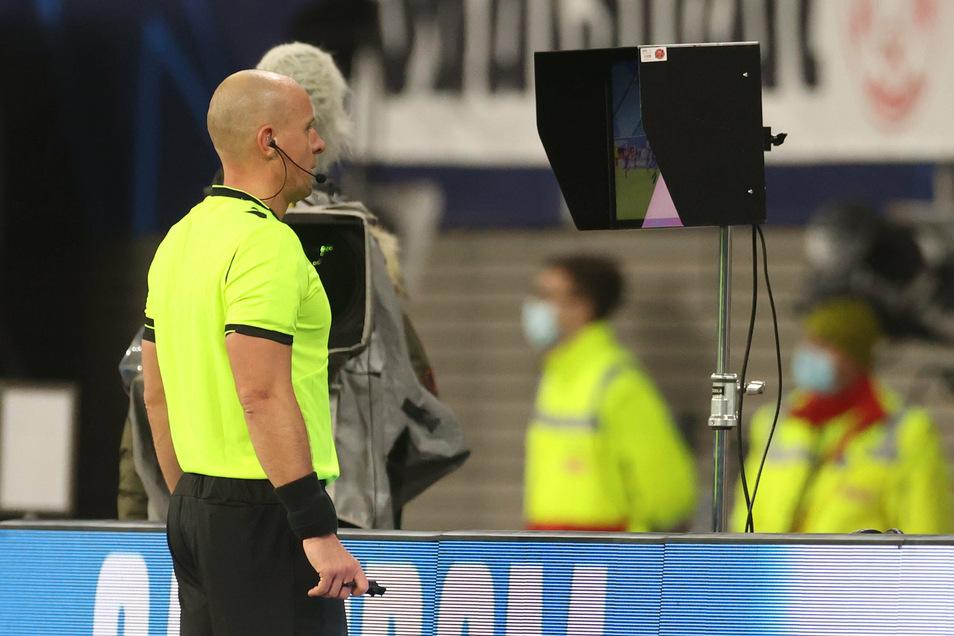 Schiedsrichter Szymon Marciniak aus Polen schaut sich die spielentscheidende Szene noch einmal auf dem Bildschirm an und entscheidet dann auf Elfmeter für Leipzig.