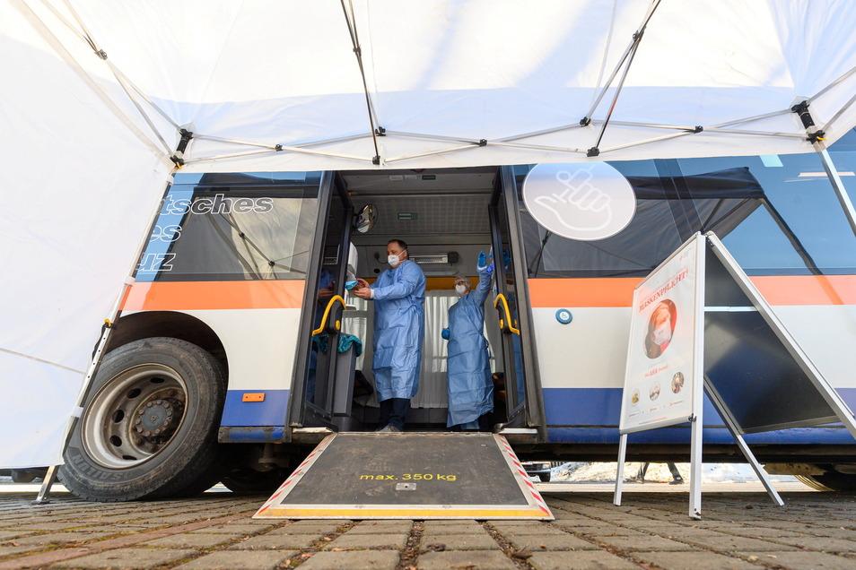 Ein Impfarzt und eine Impfhelferin bereiten sich vor Beginn des Testlaufs in einem sogenannten rollenden Impfzentrum, einem umgebauten Linienbus, auf die Impfungen gegen Corona vor.