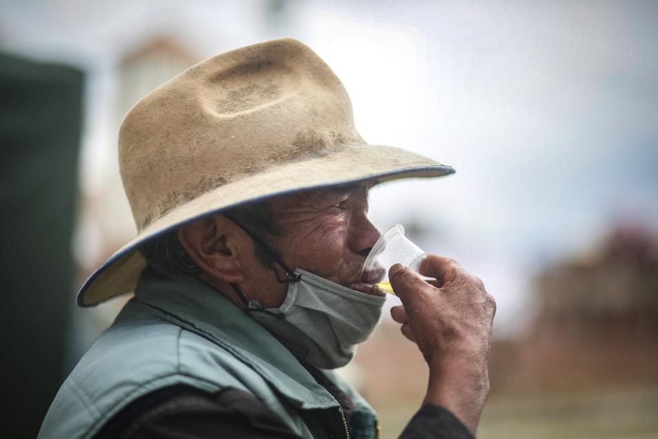 Ein Mann trinkt ein Gläschen Kamillentee, nachdem er durch eine Dampfkabine zur Vorbeugung von Atemwegserkrankungen gegangen ist. Die Kabine wurde in Bolivien vom Ministerium für Traditionelle Medizin aufgestellt.