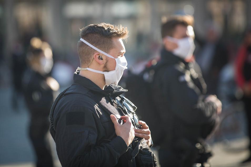 Polizisten mit Mundschutz sichern Pegida während der Corona-Krise auf dem Neumarkt.
