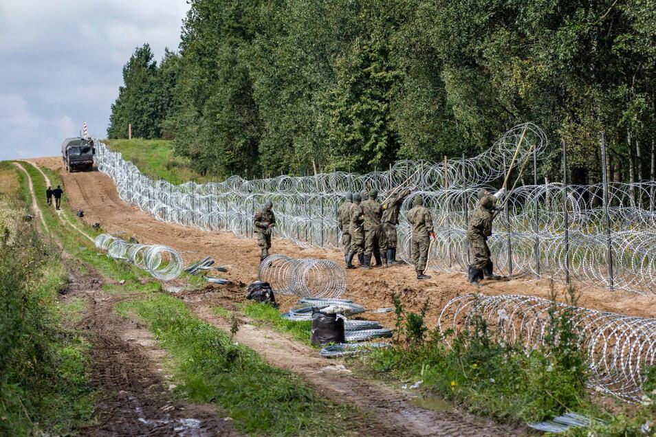 Polnische Soldaten errichten einen Stacheldrahtzaun entlang der polnisch-belarussischen Grenze. Polen hat in der Grenzregion zu Belarus den Ausnahmezustand verlängert.