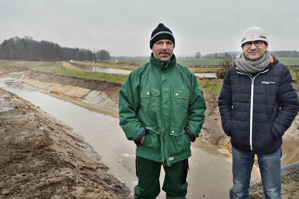 Fischwirt Jörg Greim (l.) verfolgt das Baugeschehen mit Sven Eberhardt von der Landestalsperrenverwaltung. Sie stehen vor dem Umfluter für das Schwarzwasser in Richtung Mühlgraben.