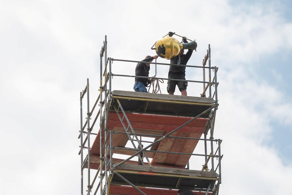Mitarbeiter der Dachdeckerei lassen die Turmkugel vom Kirchturm herunter. Die halbe Strecke absolviert sie am Seil, den Rest in einem Förderkorb.