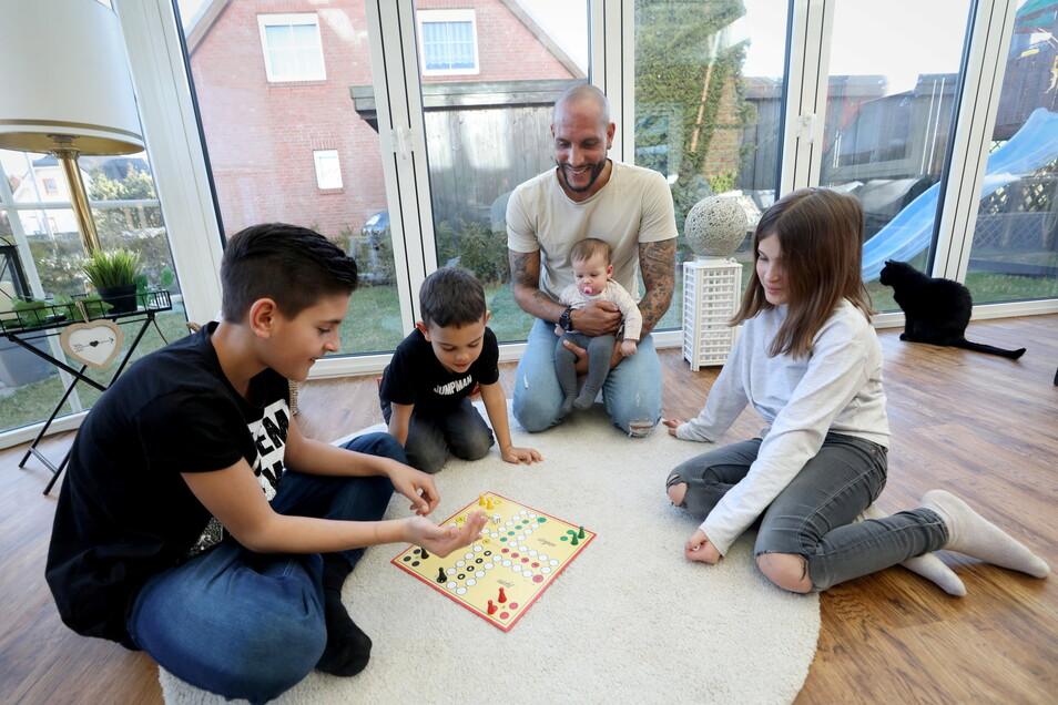 Papa ist in Elternzeit und verbringt viel Zeit mit den Kindern - drinnen beim Brettspiel ...