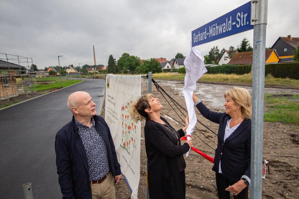 Ute Backemeier (re.) und ihre Tochter Madeleine Raschinski enthüllen das Schild mit dem Namen ihres Vaters und Opas. Die Wohngebietsstraße im neuen Wohngebiet ist nach dem Ehrenbürger und Ex-Bürgermeister von Bernsdorf benannt.