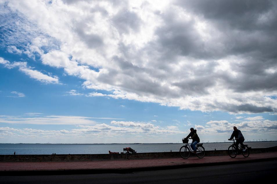 Radfahrer fahren über den Deich an der Nordseeküste.