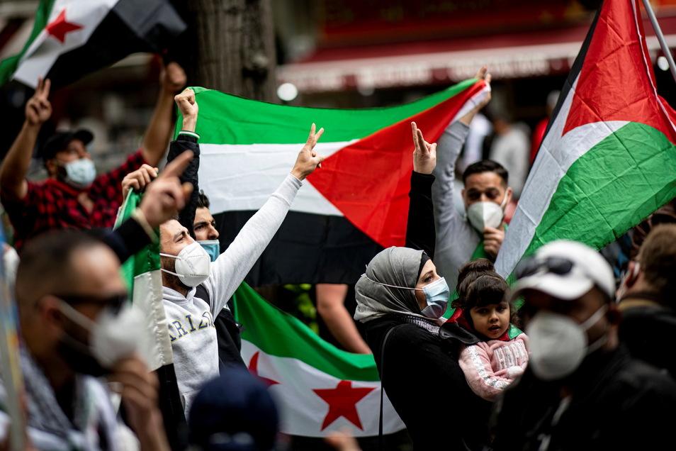 Teilnehmer der Demonstration verschiedener palästinensischer Gruppen laufen mit Palästina-Flaggen durch Berlin.