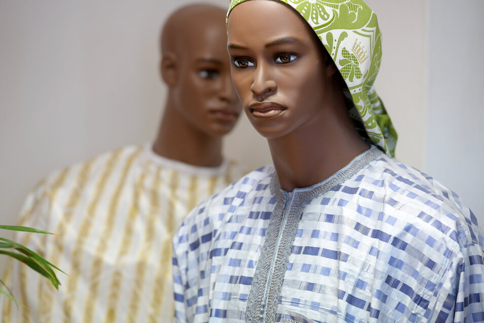 Die beiden Schaufenster-Puppen tragen große Boubou aus Damast, der bei Damino in Großschönau hergestellt wurde. Das ist eine locker fallende, weite Bekleidung, die vor allem Männer in Westafrika tragen