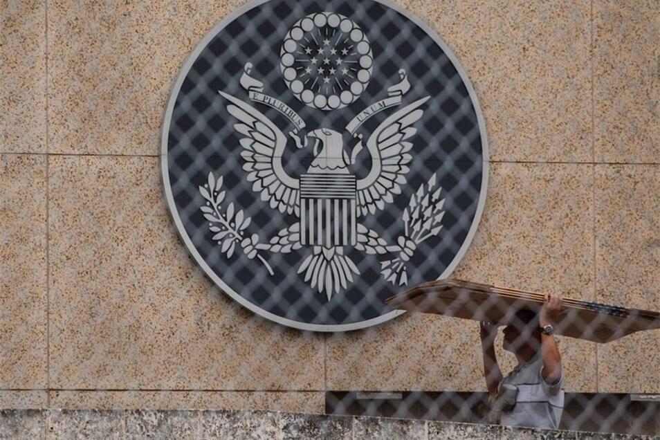 Ein Arbeiter trägt Kartons unter dem Siegel der Vereinigten Staaten entlang auf dem Gelände der US-Botschaft in Havana, Kuba.