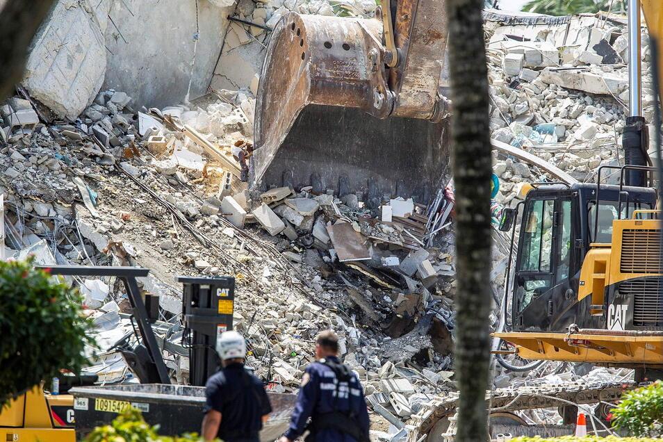Bagger graben sich durch die Trümmer der Champlain Towers South in Surfside. Zwei Wochen nach dem dramatischen Einsturz eines Wohnhauses bei Miami besteht für die Behörden so gut wie keine Hoffnung mehr, noch Überlebende in den Trümmern zu finden.