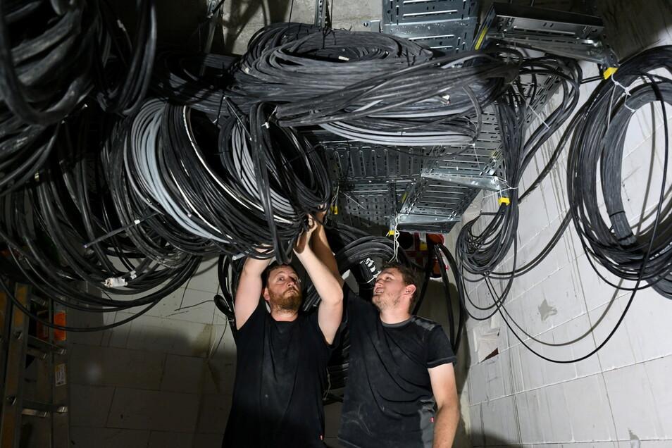 Klaus Pletl (links) und Sebastian Kerscher sortieren und bündeln die Kabel in der künftigen Zentrale der Veranstaltungstechnik.