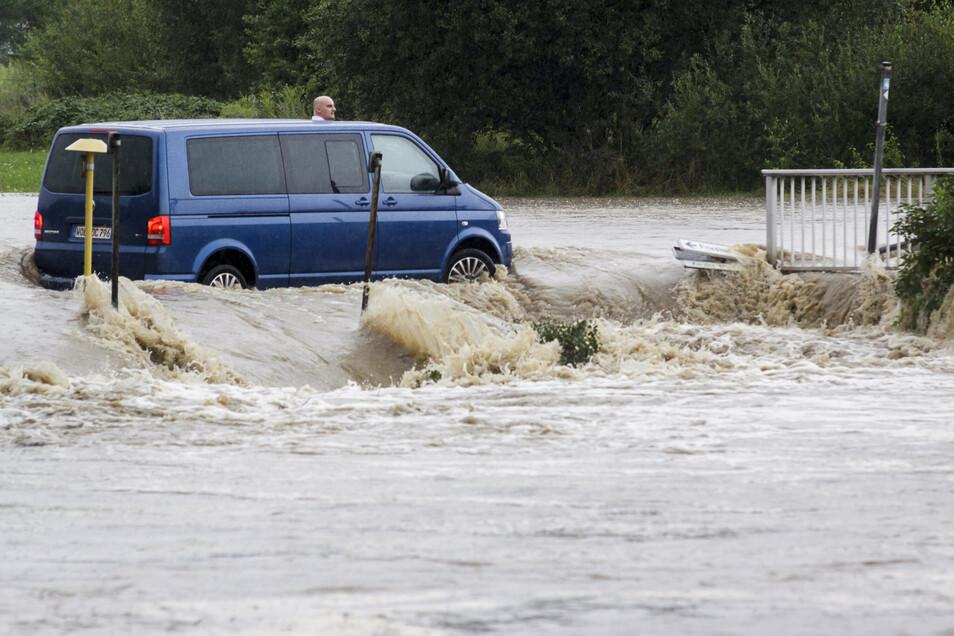 Nicht mehr geschafft: Dieser Gast einer Schulanfangsfeier wollte am 7. August 2010 in Hagenwerder sein Auto noch vor den Wassermassen in Sicherheit bringen, doch sie waren schneller.