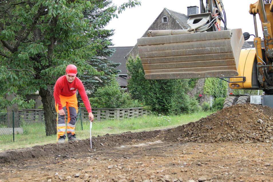 Oskar Müller misst den Abstand vom gespannten Faden bis zur Oberfläche. Die Mitarbeiter der Firma Strabag bereiten den Untergrund für das Aufbringen der Asphaltschicht vor.