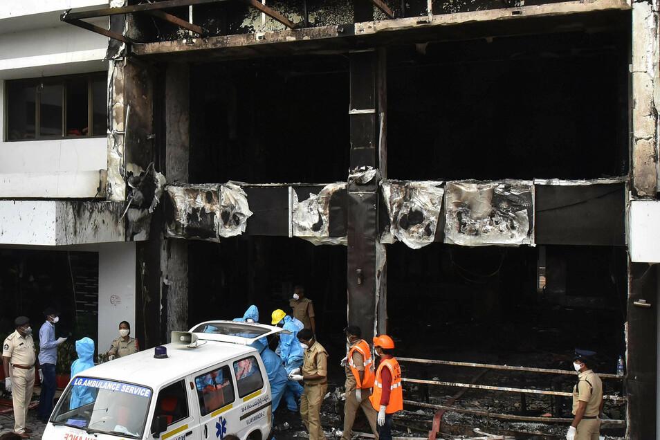 Mitarbeiter vom indischen Katastrophenschutz tragen den Leichnam eines Brandopfers aus einem Hotel im Bezirk Vijayawada in einen Krankenwagen, nachdem in einer dort eingerichteten Station zu Behandlung von Covid-19-Patienten ein Feuer ausgebrochen war.