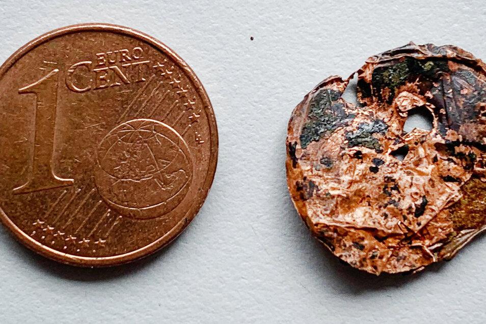 Zwei Ein-Cent-Stücke, rechts im zersetzten Zustand, liegen nebneinander.