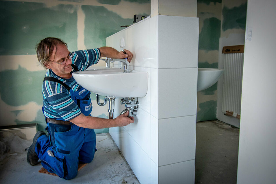 Thomas Richter baut in der Peter-Apian-Turnhalle in Leisnig Sanitäranlagen ein.