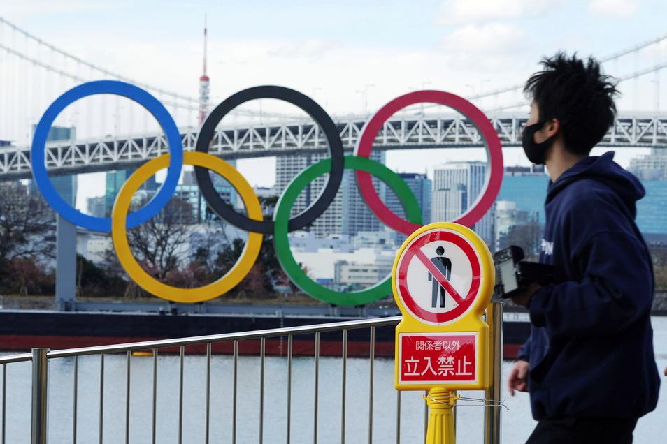 Ein Mann mit einem Mund-Nasen-Schutz geht in der Nähe der im Wasser schwimmenden olympischen Ringe im Stadtteil Odaiba vorbei.