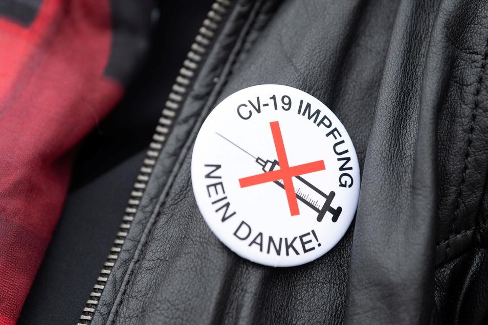 Eine Frau trägt bei einer Wahlkampfveranstaltung der AfD in Görlitz diesen Sticker. Sachsen bleibt weiter das Bundesland mit der niedrigsten Impfquote.