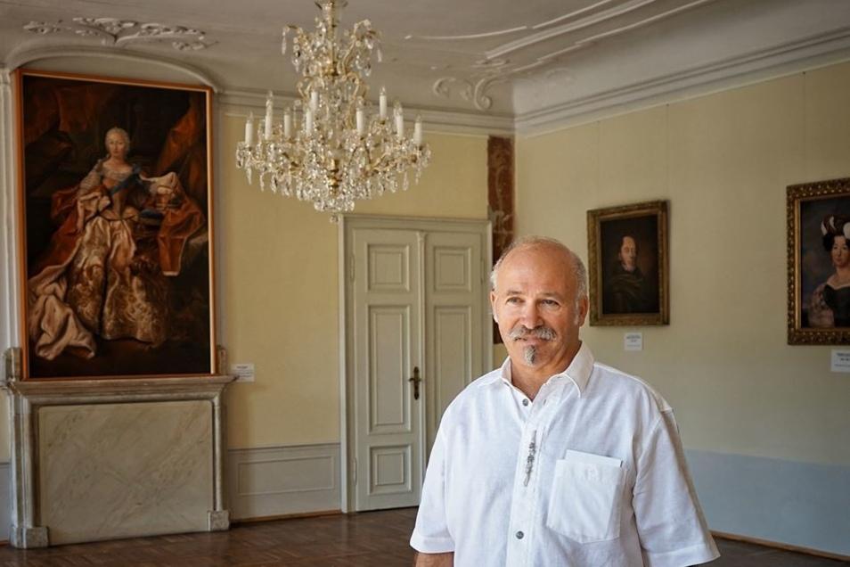 Roland Schwenke im Gartensaal des Schlosses vor seinen Bildern.
