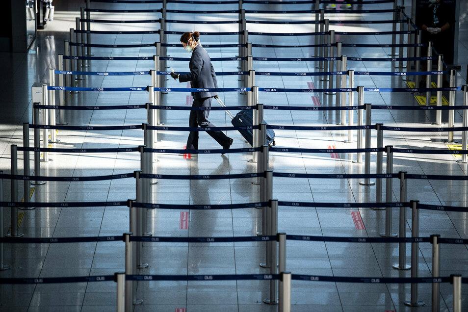 Eine einzelne Frau mit Mundschutz geht am Flughafen Düsseldorf zu einem Check In-Schalter.