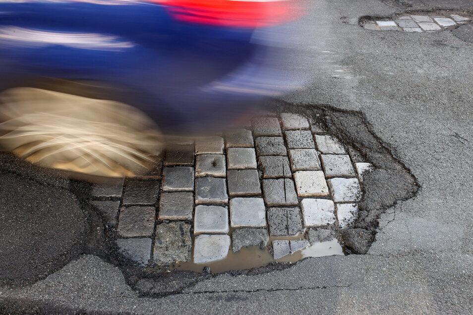 Ein Auto fährt in Leipzig über eine Straße mit Schlaglöchern. Vor allem der Wechsel aus Frost und Tauwetter setzt den Straßen zu.