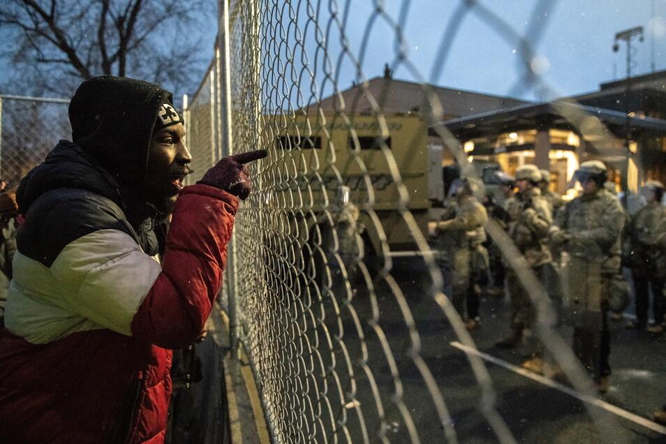 Ein Demonstrant diskutiert vor dem Hauptquartier des Brooklyn Center Police Departments mit Polizisten. Breonna Taylor, George Floyd - und nun auch Daunte Wright: Die Liste der von der Polizei in den USA getöteten Schwarzen ist erneut länger, die Debatte