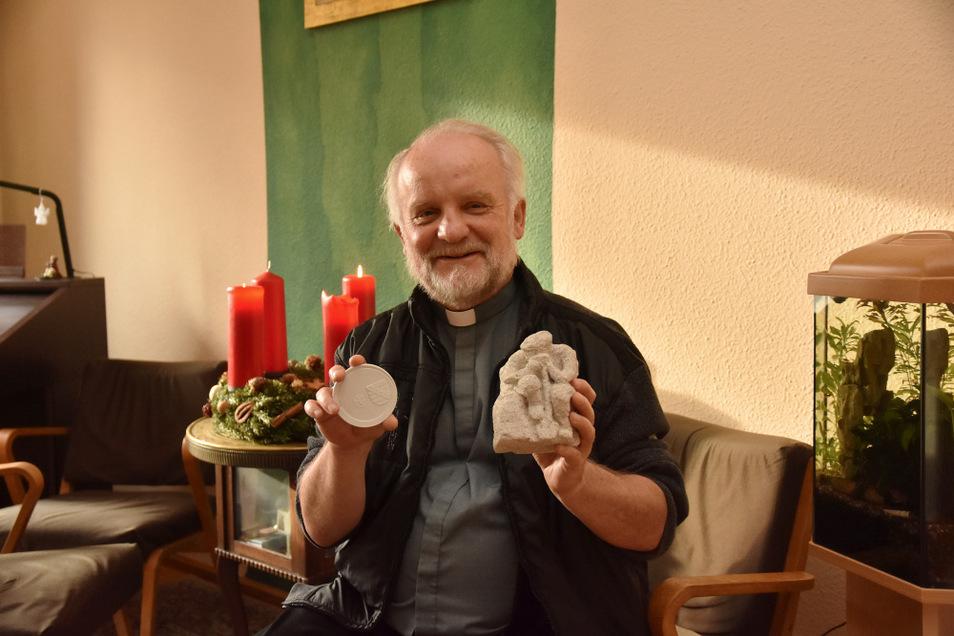 In seiner rechten Hand die Medaille vom Freistaat, in seiner Linken die Plastik der Bausoldaten von Prora – Pfarrer Peter Paul Gregor wurde für sein Engagement in der Wendezeit geehrt.