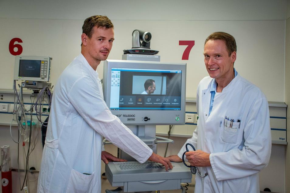 Chefarzt Dr. med. Roland Pfützer (rechts) und Matthias Richter, Leiter der Notaufnahme erklären an einem neuen Gerät im Klinikum Döbeln die telemedizinische Behandlung von Schlaganfall-Patienten.