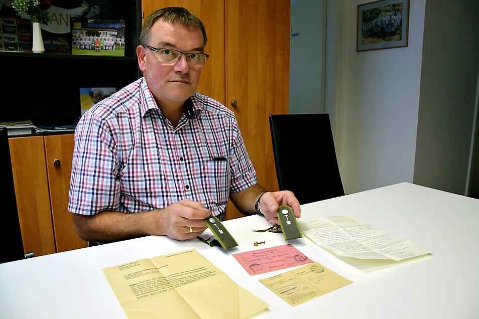 Winfried Florian mit den Schulterklappen seiner Bausoldaten-Uniform der DDR-NVA und Schriftstücken aus der damaligen Zeit.