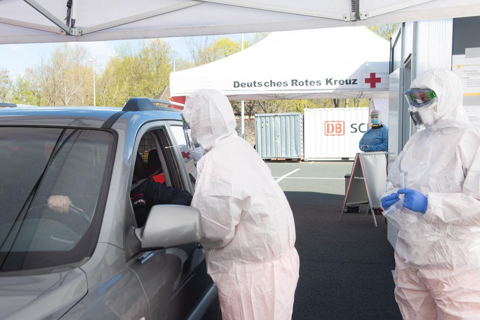 Mitarbeiter sind in Schutzanzügen im Dresdner Corona Test-Drive-in und testen im Auto.